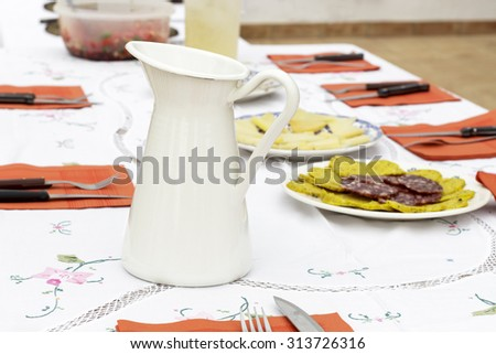 White pottery jar in table with dishes of foods at background