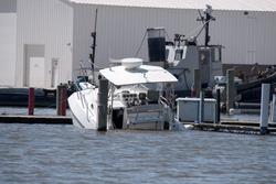 white power boat sinking in marina slip