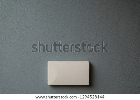 White power outlet cover copy space with blue-grey wall background.
