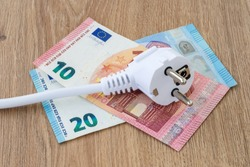 White power plug on euro banknotes over a brown wooden surface. Cost of electricity and expensive energy concepts. Top view.