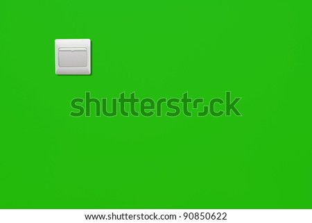 White power switch on a green wall of a energy saving room