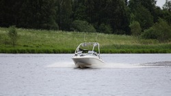 White powerboat with targa fast float on calm river water on green grassy shore with forest background at summer day, front view, active outdoor recreation watersports in Europe