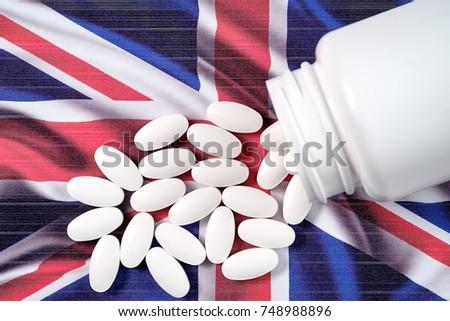 White prescription pills spilling over UK flag