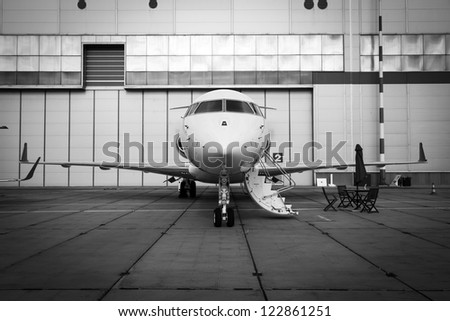 white private jet and open ladder at the airport on a background cloudy sky