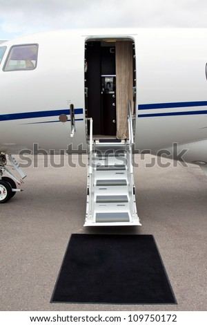 white private jet and open ladder, black carpet at airport