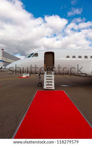 white private jet and open ladder, red carpet at the airport on a background blue sky
