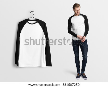 Shutterstock White pullover, long sleeve baseball t-shirt on a man in jeans, isolated mockup. Hanging t-shirt long sleeves, against empty wall.