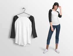 White pullover, long sleeve baseball t-shirt on a young woman in jeans and baseball cap, isolated mockup. Hanging t-shirt long sleeves, against empty wall.