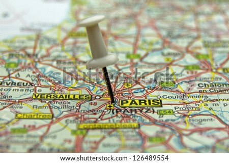 white push pin pointing at Paris, France