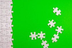 White puzzle on green background. Random and unfinished concept. Blank copy space..