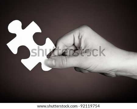 White puzzle piece solution in hand on a dark background.