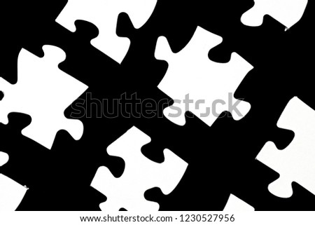 White puzzle pieces against a black background with a certain distance between the individual parts - concept for sub-steps or sub-elements of a large whole presented with puzzle pieces #1230527956