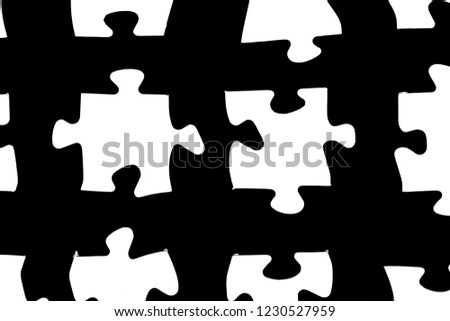 White puzzle pieces against a black background with a certain distance between the individual parts - concept for sub-steps or sub-elements of a large whole presented with puzzle pieces #1230527959