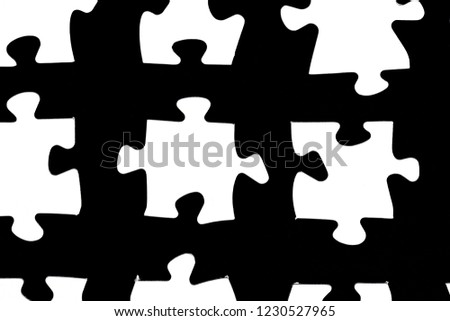 White puzzle pieces against a black background with a certain distance between the individual parts - concept for sub-steps or sub-elements of a large whole presented with puzzle pieces #1230527965