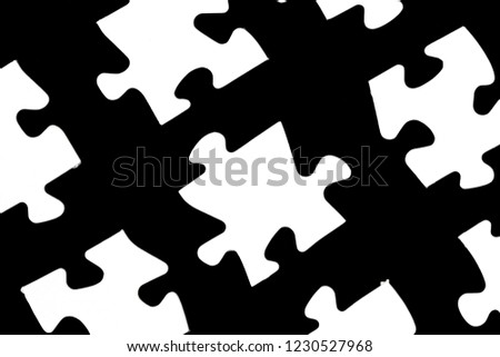 White puzzle pieces against a black background with a certain distance between the individual parts - concept for sub-steps or sub-elements of a large whole presented with puzzle pieces #1230527968