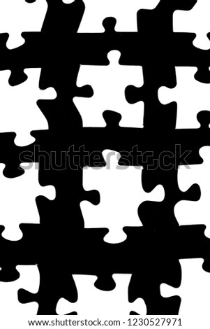 White puzzle pieces against a black background with a certain distance between the individual parts - concept for sub-steps or sub-elements of a large whole presented with puzzle pieces #1230527971