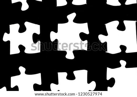 White puzzle pieces against a black background with a certain distance between the individual parts - concept for sub-steps or sub-elements of a large whole presented with puzzle pieces #1230527974