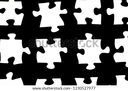 White puzzle pieces against a black background with a certain distance between the individual parts - concept for sub-steps or sub-elements of a large whole presented with puzzle pieces #1230527977