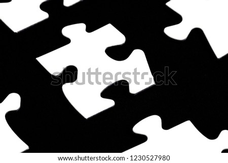 White puzzle pieces against a black background with a certain distance between the individual parts - concept for sub-steps or sub-elements of a large whole presented with puzzle pieces #1230527980
