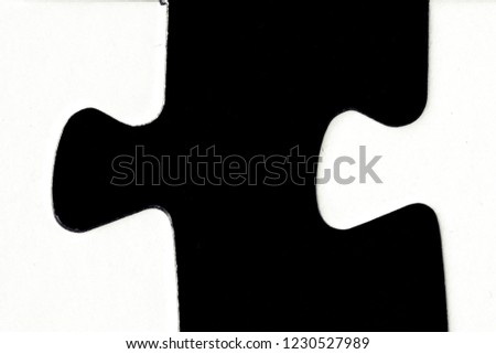 White puzzle pieces against a black background with a certain distance between the individual parts - concept for sub-steps or sub-elements of a large whole presented with puzzle pieces #1230527989