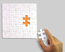 White puzzle with a piece in hand (Clipping Path)