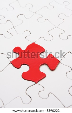 White puzzle with one bright red piece