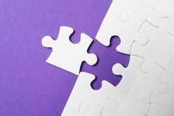 White puzzle with unfitting piece on purple background, flat lay