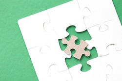 white puzzles on a pink background, folded puzzle, one piece is missing, instead a piece from another puzzle, an unsuitable part, unlike others, copy space