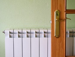 White radiator in a corridor with a wooden and glass door, green wall with stippled paintwork. Warm home