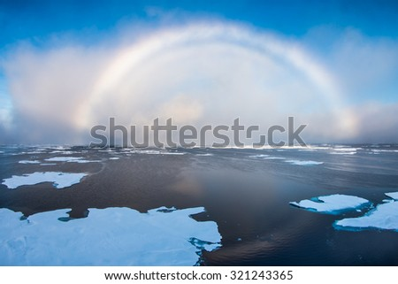 White rainbow over Arctic sea with floating ice in East-Siberian sea, Arctic ocean. White rainbow is rare meteorological phenomenon.