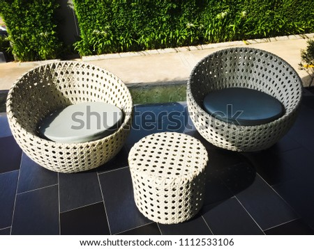 White rattan chair set on gray tile floor, Grass wall background. #1112533106