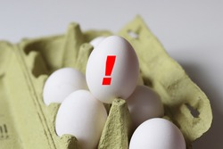 white raw eggs in a carton with warning signs - salmonella infection risk and high cholesterol risk concept