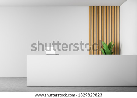 White reception desk with laptop on it standing in modern office with white and wooden walls and concrete floor. 3d rendering