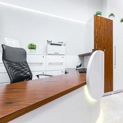 White reception with long, wooden desk and black office chair