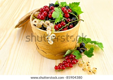 White, red and black currant with green leaves in a bowl  from birch bark on a wooden board