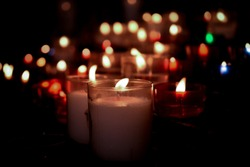 White, red, green, and blue candles with bokeh and black vignette