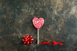 White-red striped lollipop in the shape of a heart on a dark aged concrete background. Below are two small red bows and one large, top view. Valentines day concept, empty space for text