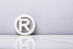 White Registered Trademark Sign Leaning On Wall