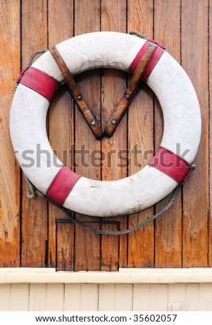 White rescue buoy hanging on wooden wall of a boat