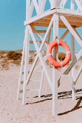 white rescue post with a lifebuoy. on a Sunny summer day. Coastal architecture. Wooden rescue post
