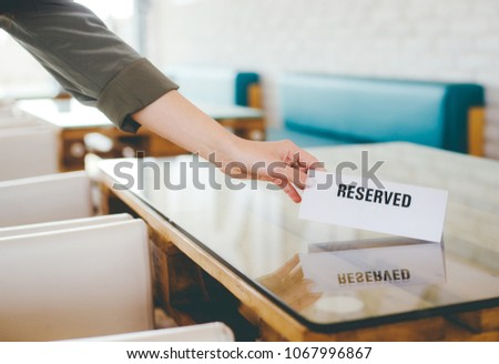 White reserved sign in hands of waiter on a table in restaurant