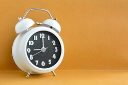 White retro alarm clock on light brown background with copy space