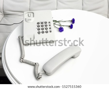 White retro landline phone and blue fresh cornflowers bouquet on a wooden white round table.  Handset lying separatly. It is disconnected. It is out of line. It is behind of love #1527515360