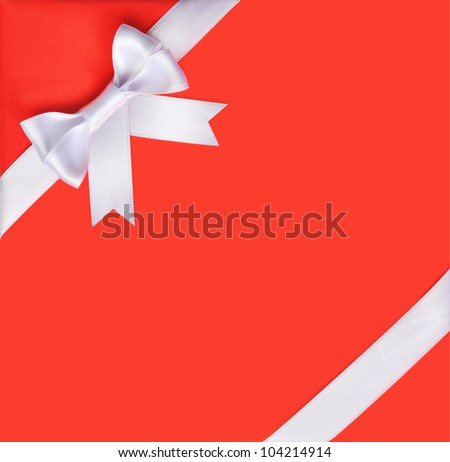 White ribbon bow on a red background