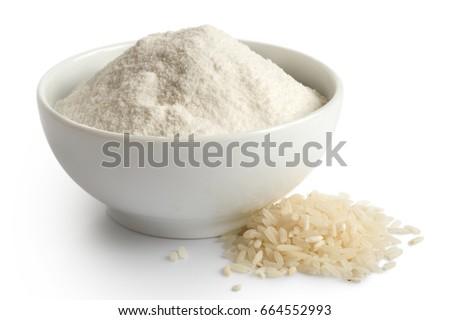 White rice flour in white ceramic bowl isolated on white. Spilled long-grain rice. #664552993