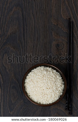 white rice in a bowl and chopsticks on dark background, top view, vertical