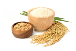 White rice in wooden bowl with paddy rice ears and green blades isolated on white background.