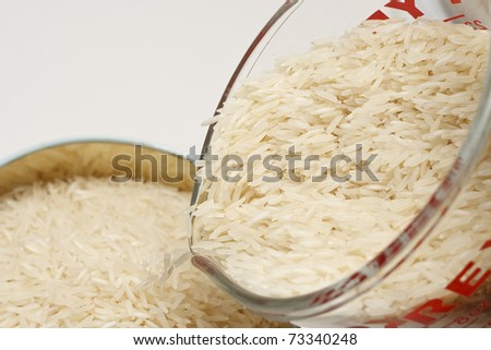 White Rice Pouring from Glass Measuring Cup Into Canister