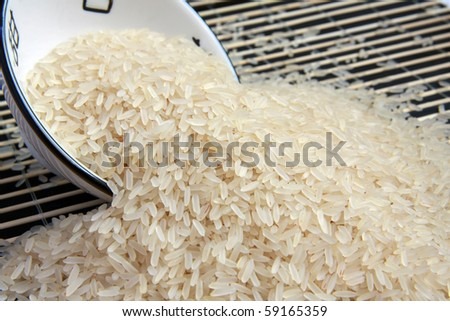 White rice spilled from round bowl on bamboo carpet