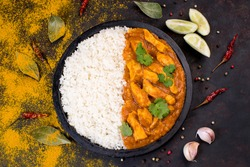 White rice with chicken and vegetables and curry sauce. Indian dish rice with vegetables and chicken on a black plate with lemon and red hot pepper and garlic on the table..